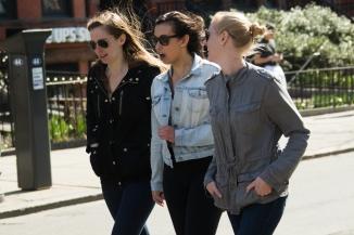 Three students walk down Newbury Street after watching the marathon on 18 April 2016.
